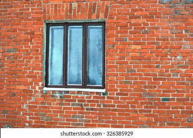 Frozen window in a wall of red bricks