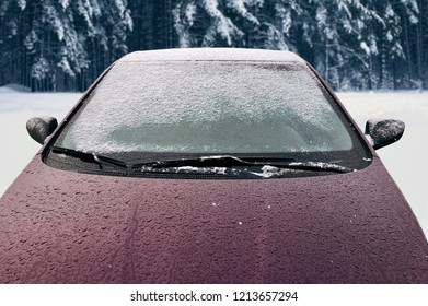 Frozen winter car covered snow, view front window windshield and hood on snowy background