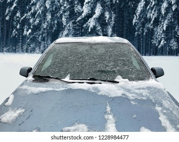Frozen winter car covered snow in forest, view front window windshield and hood on snowy background