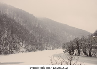 Frozen winter lake with cold forest in Lillafured, Miskolc, Hungary. Lake with ice and snowy mountain. Winter landscape. Travel in Hungary. Winter weather concept. Snowy mountain in frosty fog.