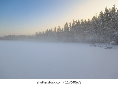 The frozen winter lake in wood under snow