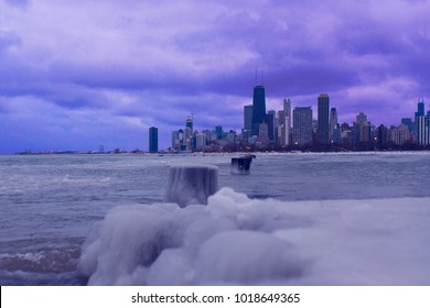 A frozen, winter of the skyline of Chicago. A vibrant skies sits above the city and Lake Michigan is frozen in the foreground.