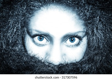 frozen woman in a fur coat looking straight into the camera with blue eyes
