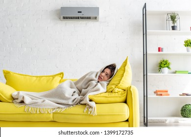 frozen woman warming with blanket while lying on yellow sofa under air conditioner at home