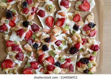 Frozen yogurt bark with various fruit strawberry, banana, nectarine, kiwi, raspberry, blackberry and stevia. Healthy, sugar free and gluten free snack. Top view.