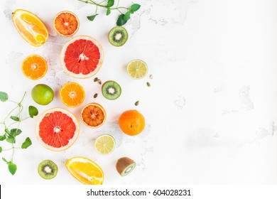 Fruit background. Colorful fresh citrus fruit on white table. Orange, tangerine, lime, kiwi, grapefruit. Flat lay, top view, copy space