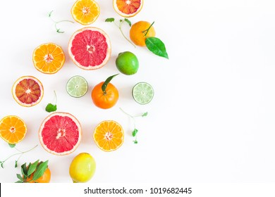 Fruit background. Colorful fresh fruits on white table. Orange, tangerine, lime, lemon, grapefruit. Flat lay, top view, copy space.