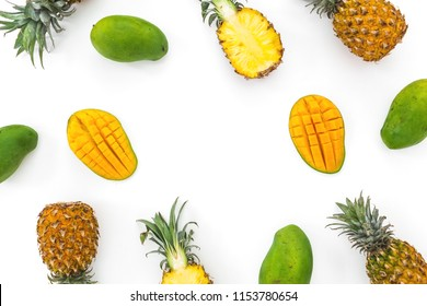 Fruit background of pineapple and mango fruits on white background. Flat lay, top view. Tropical concept.