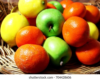 A fruit basket with lemons, oranges and apples