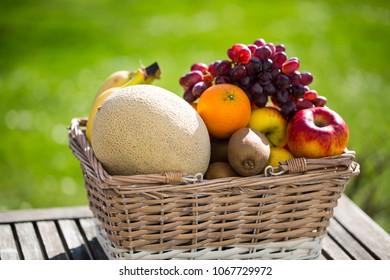 Fruit basket on table, green background
