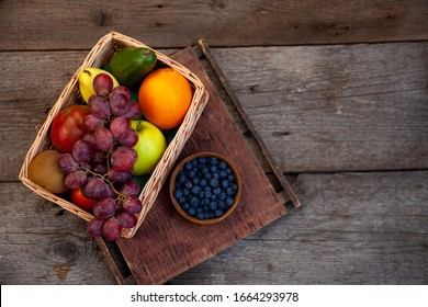 Fruit basket on a wooden kitchen table. Assorted fruits, set. Different multi-colored fruits. Vitamin nutrition.