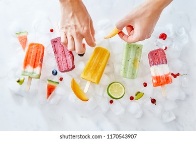Fruit berry ice lolly on ice cubes. A woman's hand decorates ice cream with pieces of fresh fruit fruit. Flat lay