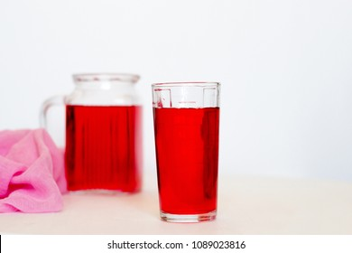 Fruit and berry red juice in glasses and jug on a white background.