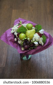Fruit bouquet of apple, lime, pear, chrysanthemum, grapes in paper packaging.