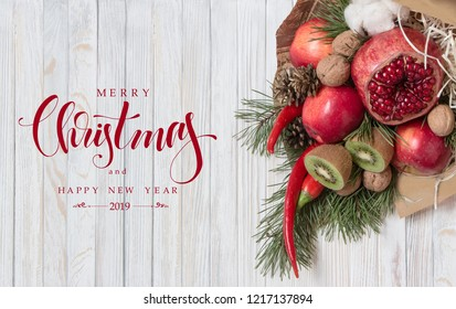 Fruit bouquet with exotic ingredients, Christmas tree brunches on white wood background and modern hand drawn lettering. Holiday card with wishes