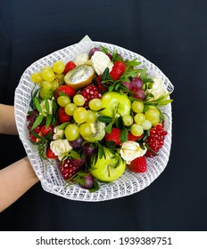 Fruit bouquet in a white net of grapes, apples, pomegranates, kiwis, strawberries, decorated with white roses and green twigs.