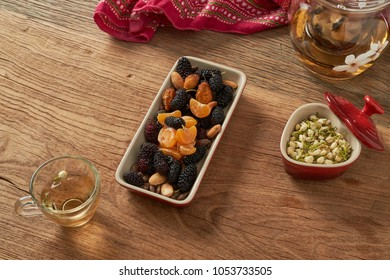 Fruit bowl of mulberry, orange, berry, nut combination on wooden table.