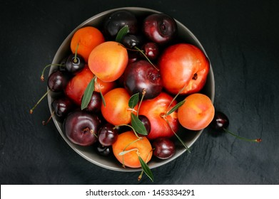 Fruit bowl. Seasonal fruits with green leaves in a bowl n rustic dark background, top view. Organic fresh fruit, peach, plum, aprocot, cherry.