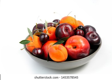 Fruit bowl. Seasonal fruits with green leaves in a bowl over white background, top view. Organic fresh fruit, peach, plum, aprocot, cherry.