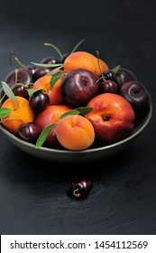 Fruit bowl. Seasonal fruits with green leaves in a bowl on rustic dark background, top view. Organic fresh fruit, peach, plum, aprocot, cherry.