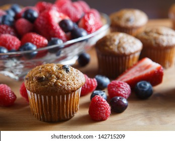 Fruit and bran muffins alongside bowl of fresh blueberries, raspberries and strawberries