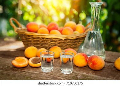 Fruit brandy in shot glass with fresh apricots on the table