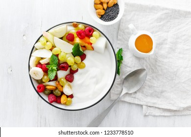Fruit breakfast and natural yoghurt bowl. Grapes, peach, apple, melon, raspberry, almond, honey and greek yogurt. Healthy food concept on white background, top view flat lay