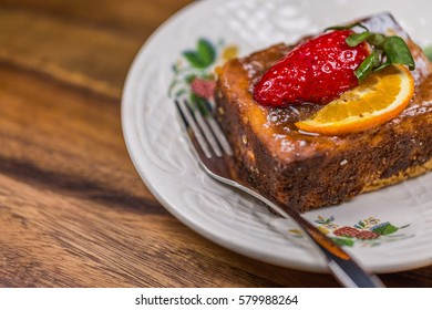 Fruit Cake on saucer with fork on wooden table