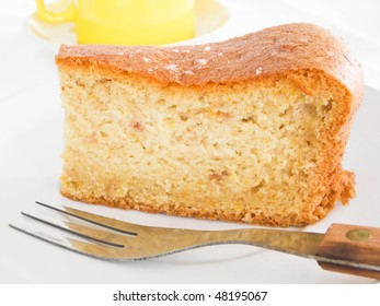 Fruit Cake Slice at Breakfast with fork on white dish.