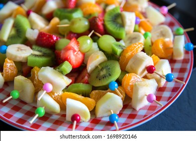 Fruit canape for a buffet on a plate. Sweet treats for a holiday, anniversary, birthday. Delicious and healthy food. Vegetable vitamins. Mix of tangerine, Apple, strawberry, grape, banana