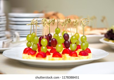 Fruit canape. Portional canapes from grapes, strawberries and pineapple