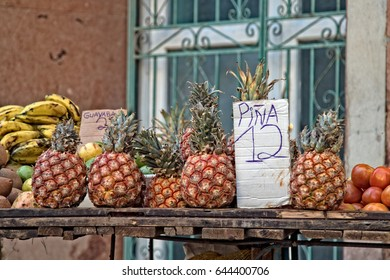 A fruit cart filled with pineapple and bananas on a city street in old Havana.