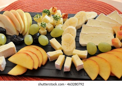 Fruit and cheese platter - black plate on a red table mat. Bananas, grapes, pear and peaches with brie and Gouda cheese.