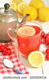 Fruit cherry tea with slice of lemon in glass mug, old teapot, red checkered tablecloth, teaspoon sugar, fresh cherries and lemons in foreground