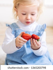 Fruit for children: A little two-year-old girl in a blue sundress holds a big strawberry fruit in her hand. Portrait.