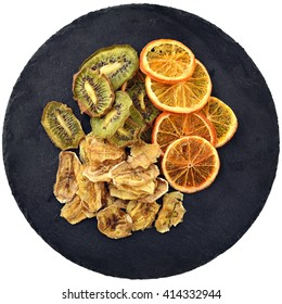 Fruit chips. Healthy and fashionable snack. Dried slices of orange, kiwi and banana on a black circle slate. Top view