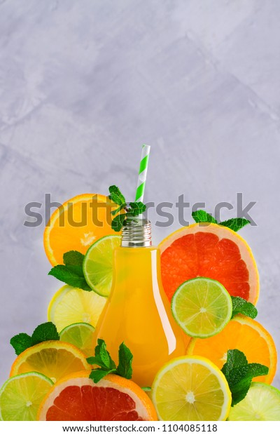 Fruit citrus juice in lamp-shaped glass with green striped straw and fresh  fruits slices orange, grapefruit, lemon, lime and mint leaves on gray concrete background, close-up, place for copy space.