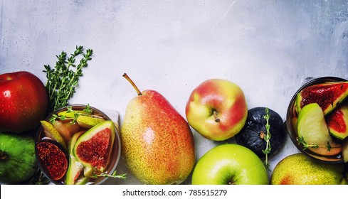 Fruit cocktail with wine, pears, apples and figs, gray background, top view