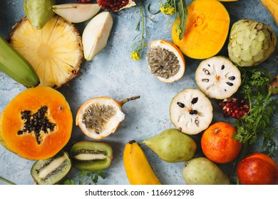 Fruit colorful pattern. fresh Papaya, cherimoya, mango, maracuja, banana, pineapple, pomegranate tropical fruits over blue table. Top view.