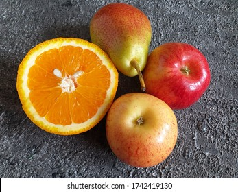 Bright fruit composition. Two pears, an apple and half an orange. Close-up on a gray background. Background, banner.