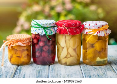 Fruit compote in jar. Garden as background. Selective focus. Homemade preserved food on table outdoor.