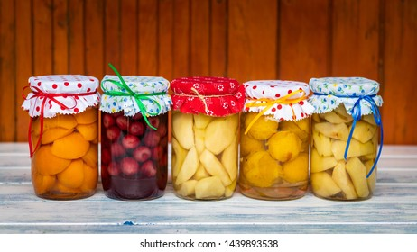 Fruit compote in jar, homemade preserved food. Variety of canned fruits on wooden table. Organic food concept.