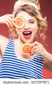Fruit Concepts and Ideas. Smiling Passionate Caucasian Blond With Two Grapefruit Slices in Front of Face. Against Red Background. Vertical Image Composition