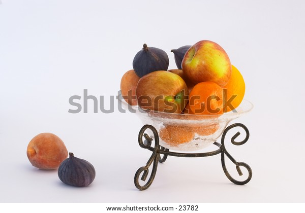 Fruit in a crackle-glass bowl on a metal stand.