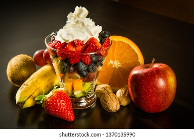 Fruit dessert with several different types of fruit. Banana, kiwi, apple, grape, orange, strawberry, blueberry, nuts, etc. Whipped cream on top.