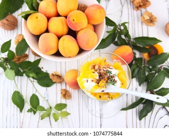 Fruit dessert with whipped cream, apricot, mint and granola