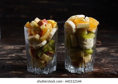 Fruit desserts made at home. 2 cups with sliced fruit. Fresh fruits on a wooden background.