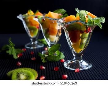 Fruit desserts, salad of pineapple, papaya, pomegranate and mint, kiwi on a dark background