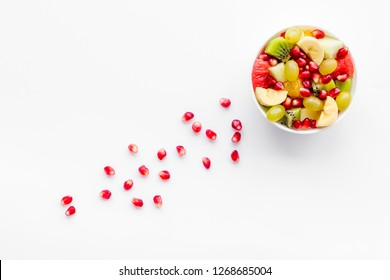 Fruit diet concept. Fruit salad with apple, kiwi and pomegranate in bowl on white background top view copy space