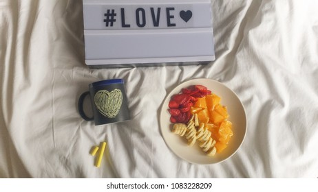 Fruit dish love sign and mug on white bed